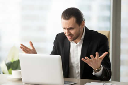 Business Owner in a Panic Looking at Laptop